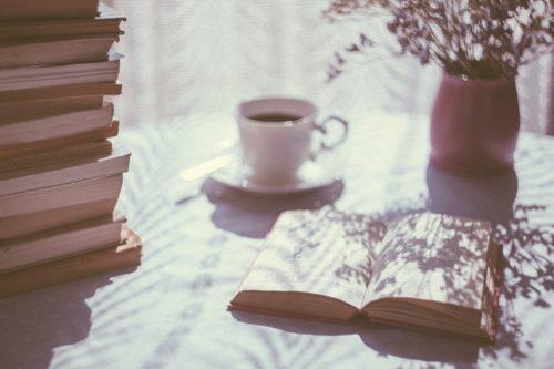 日差しが差すテーブルに置かれた本とコーヒー