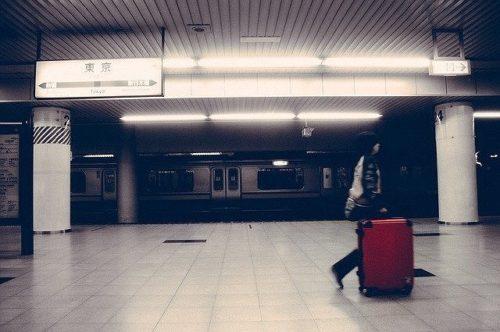 スーツケースをひいて駅構内を歩く人