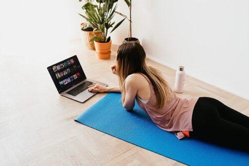 ヨガマットに寝てパソコン操作する女性