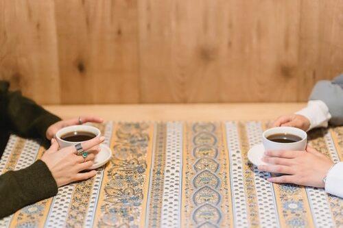 コーヒーカップを持った向かい合うふたり